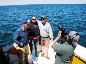 "U.S. Army veterans Elaine and Gerry Esposito of Port Leyden are guests on the Aug. 26 episode of ""Fishing Behind the Lines,"" filmed in May aboard Capt. Ernie Lantiegne's Fish Doctor charter boat. The show is hosted by Don Meissner, left. Cameraman is Roque Murray."